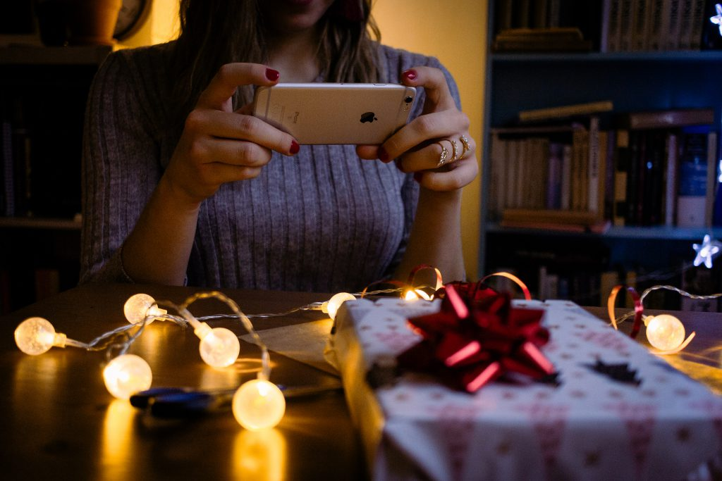 A female taking picture of a christmas gift - free stock photo