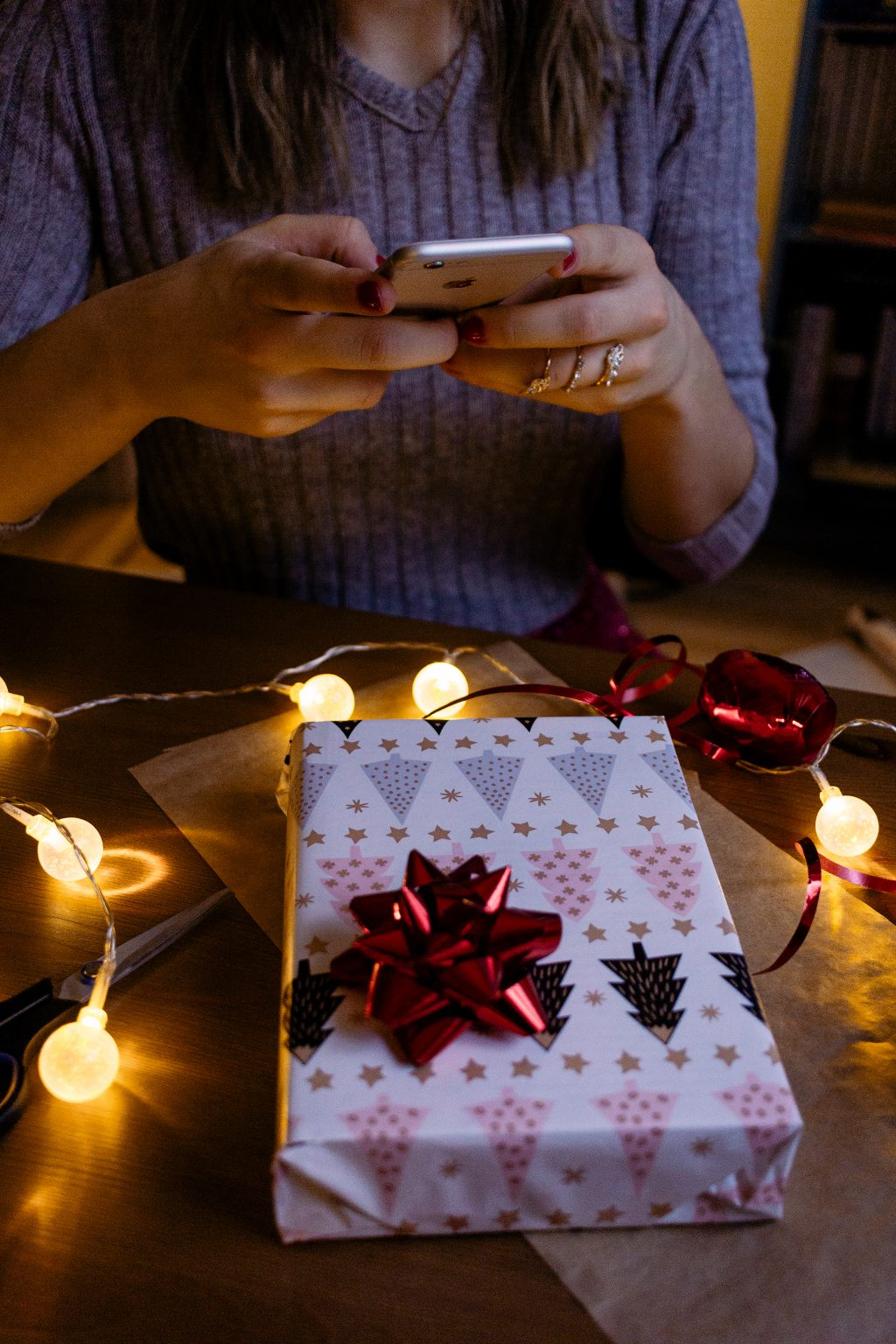 A female taking picture of a christmas gift 2 - free stock photo