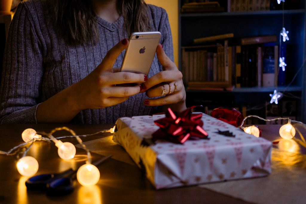 A female taking picture of a christmas gift 3 - free stock photo