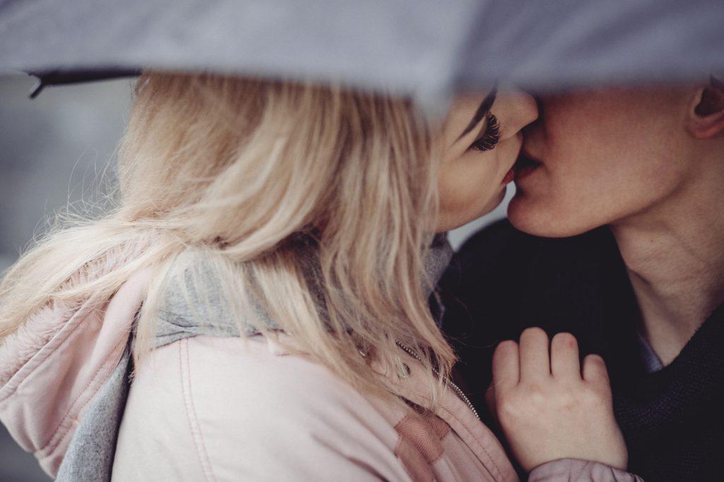 Couple kissing under an umbrella - free stock photo