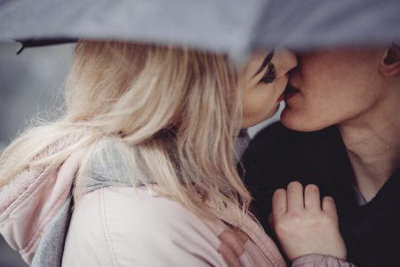 Couple kissing under an umbrella - free stock photo