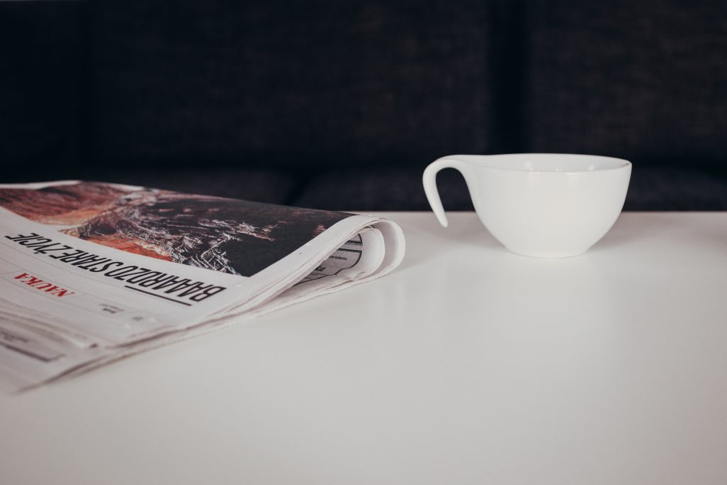 Cup of coffee and a newspaper on the table - free stock photo