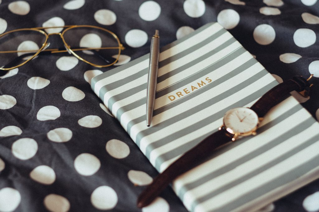 Dreams notebook and wristwatch - free stock photo