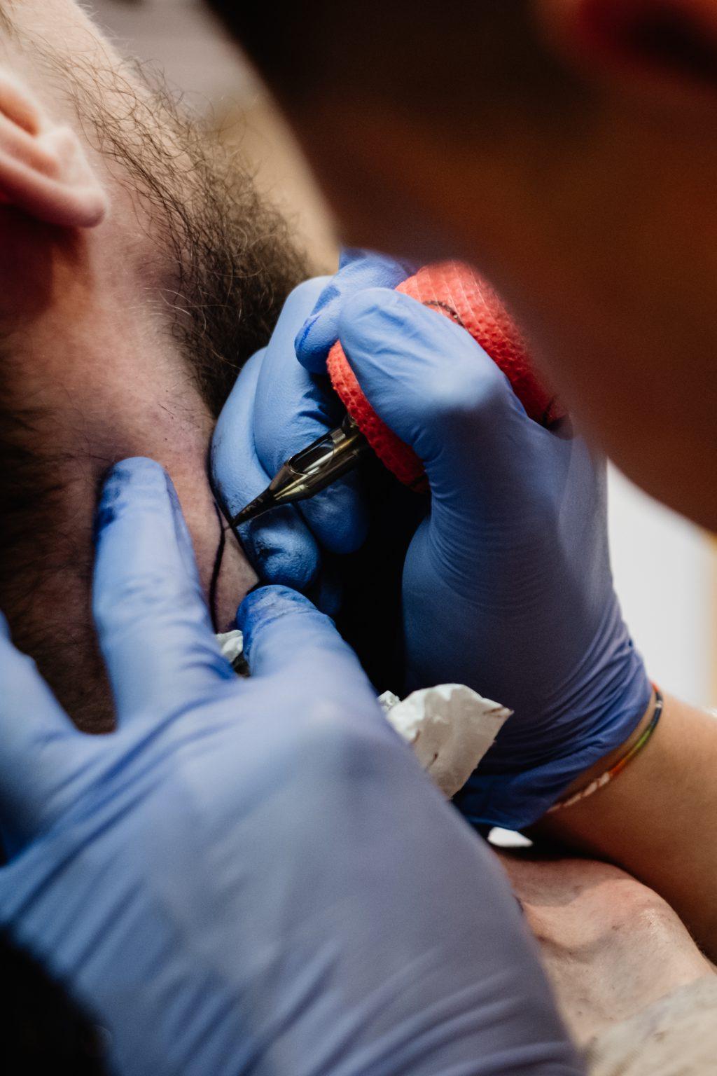 Tattoo artist at work closeup 3 - free stock photo
