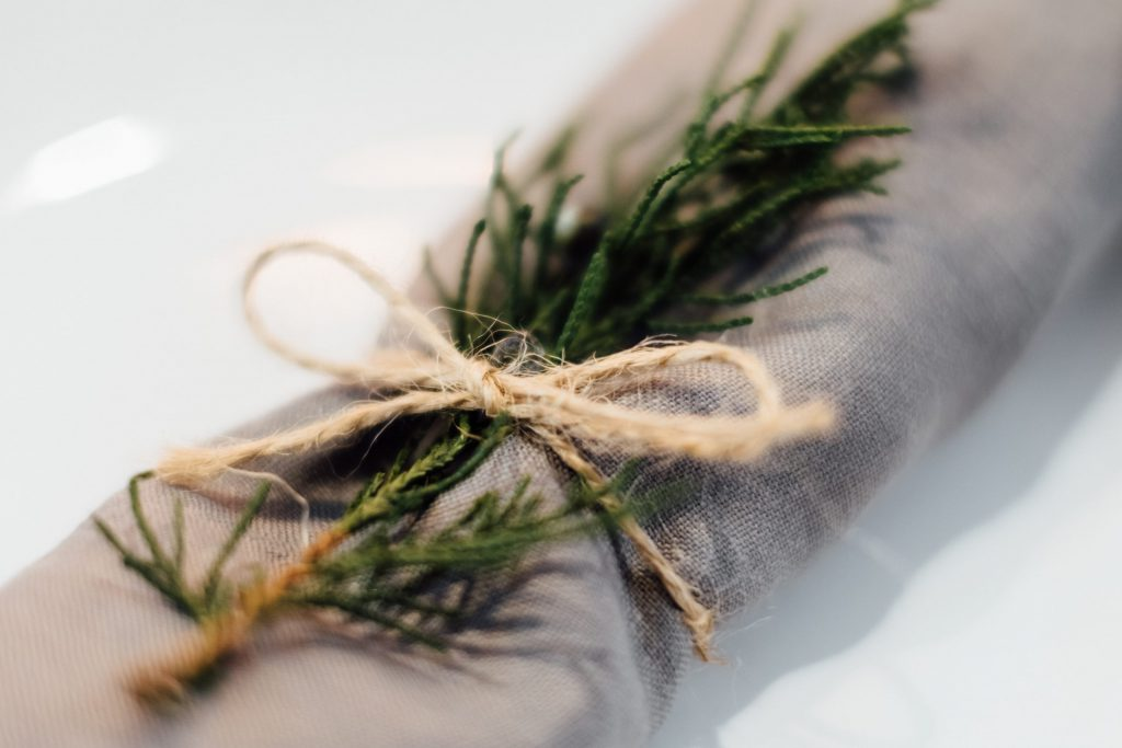Linen napkin decorated with a conifer twig closeup - free stock photo
