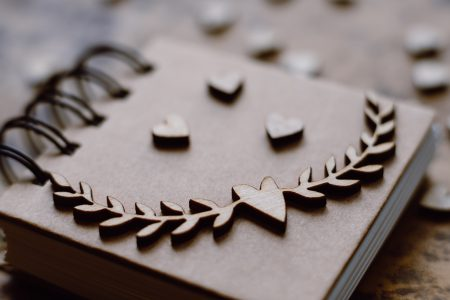 Wooden heart decorations on a notebook - free stock photo