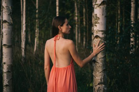 A girl in a backless dress in the woods - free stock photo