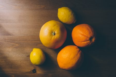 A grapefruit, oranges and lemons on a wooden table - free stock photo