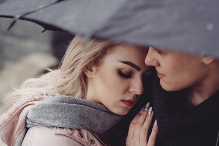 A couple hugging under an umbrella closeup - free stock photo
