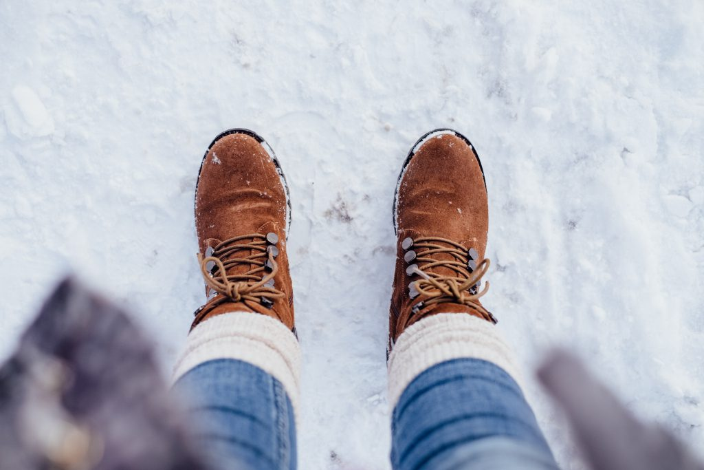Female feet standing on a snow-covered pavement - free stock photo