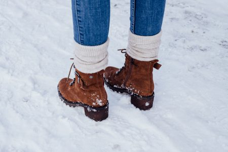 Female feet standing on a snow-covered pavement 2 - free stock photo