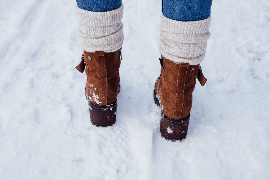 Female feet standing on a snow-covered pavement 3 - free stock photo