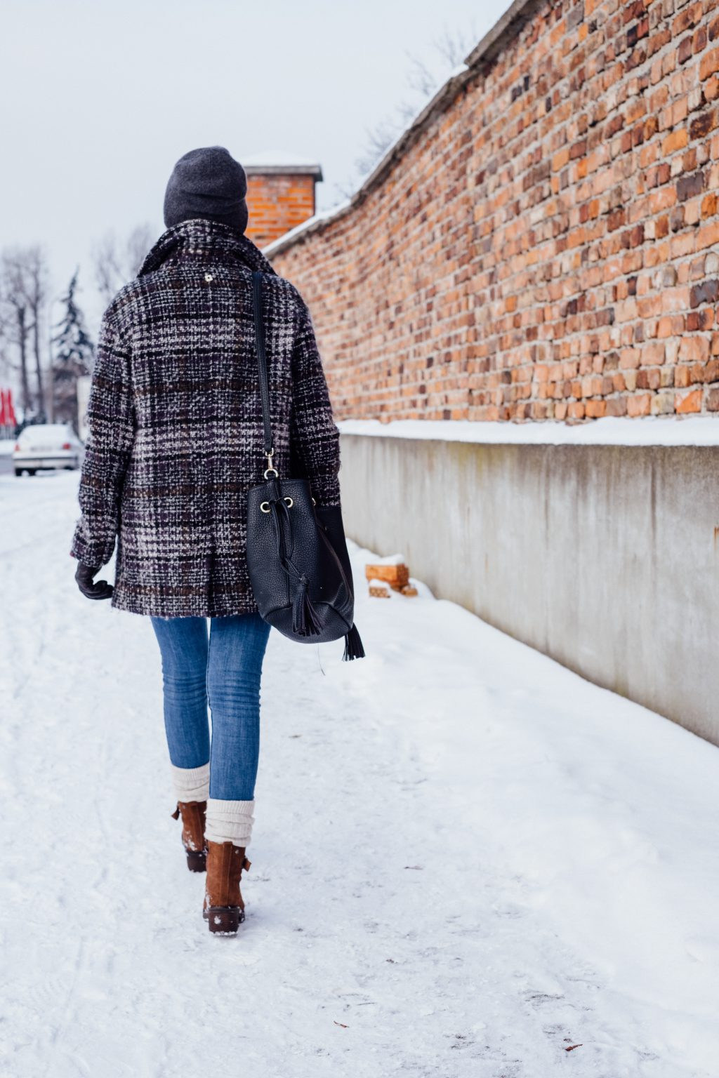A female walking on a snow-covered pavement - free stock photo