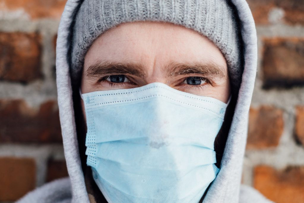 A male wearing a protective face mask closeup - free stock photo
