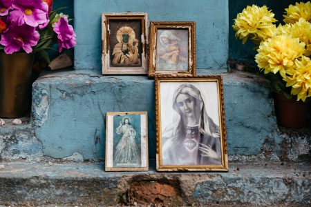Distressed catholic holy pictures placed outside a poor neighbourhood - free stock photo