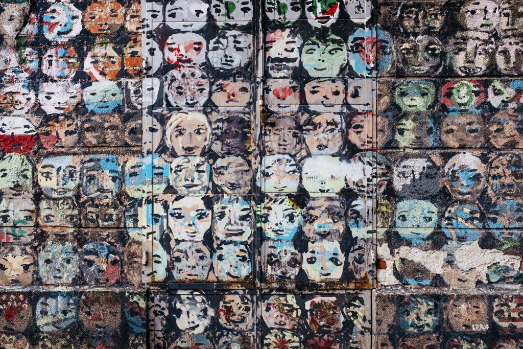 Graffiti of many cartoonlike faces on a building - free stock photo