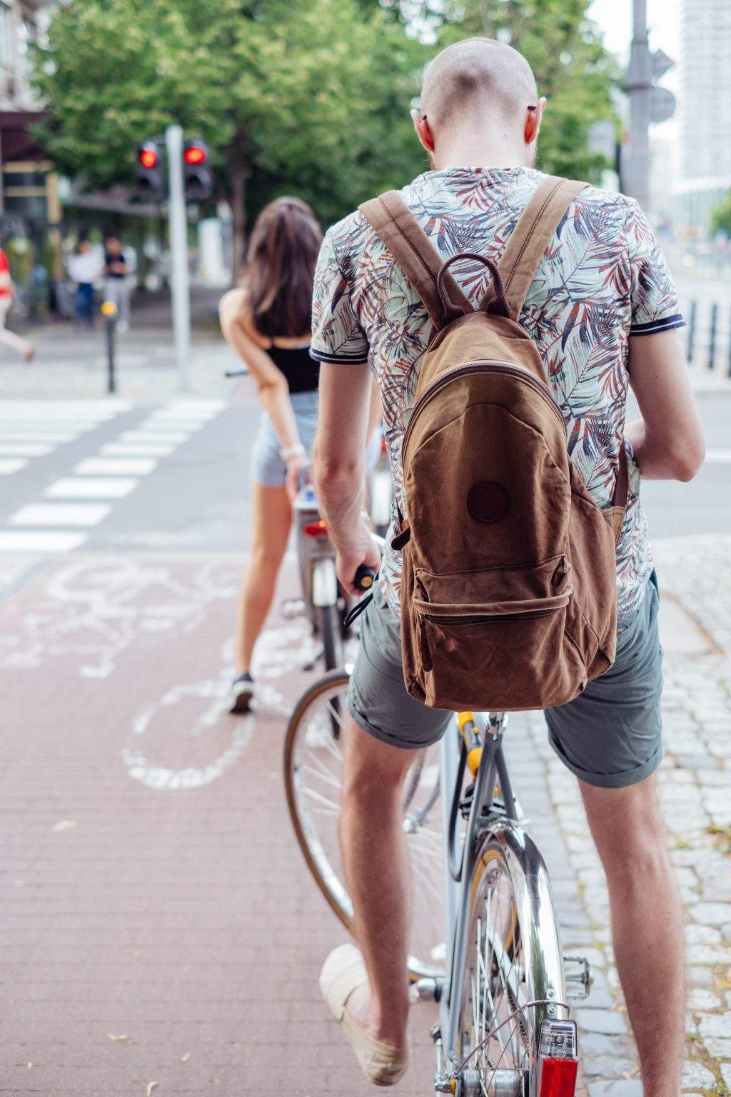 Cyclists waiting for a green light at the road zebra crossing - free stock photo