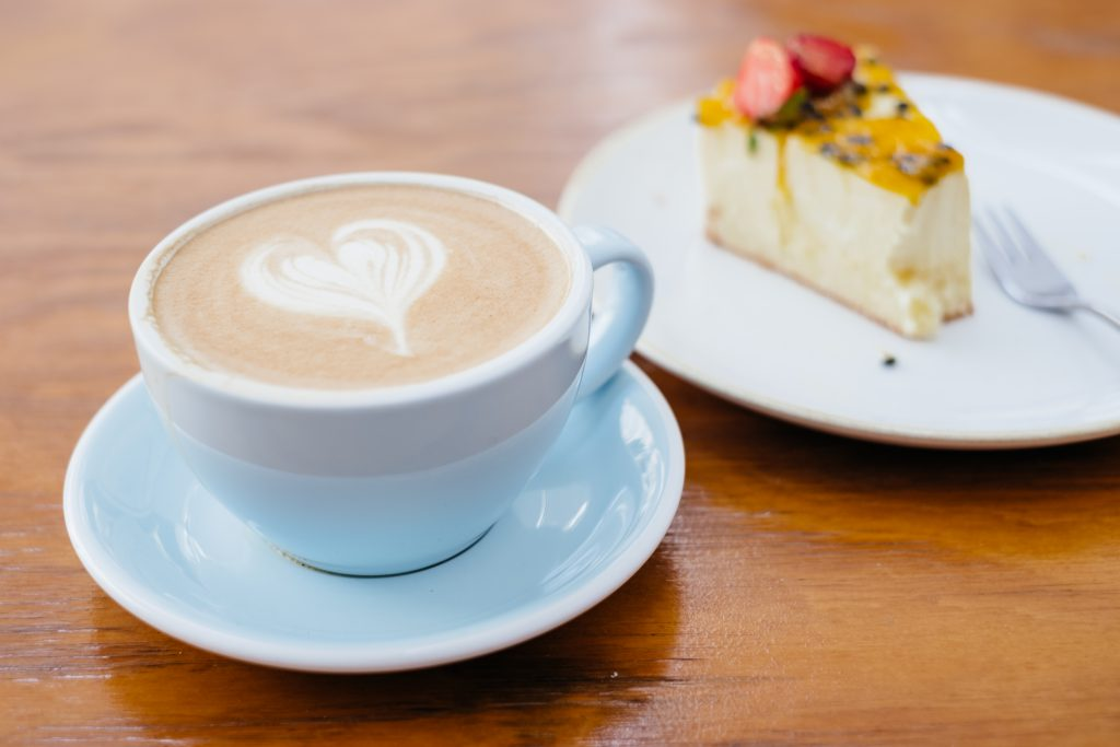Latte and a cheesecake on a café table - free stock photo