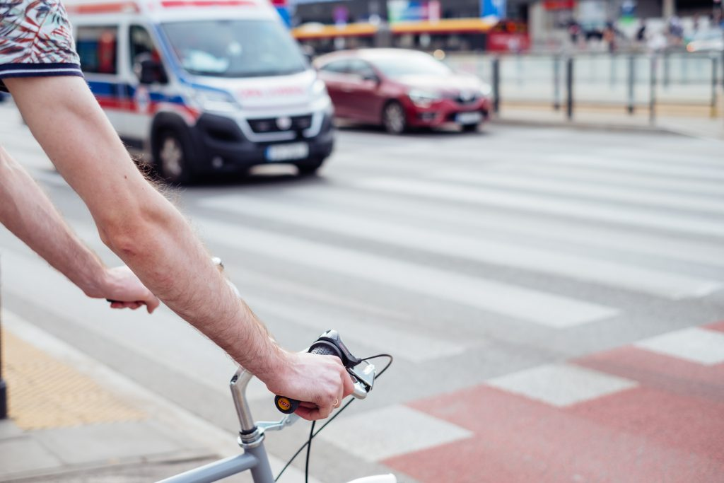 Male cyclist waiting for a green light at the road crossing - free stock photo