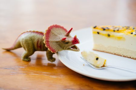 Rubber toy dinosaur about to eat a cake 2 - free stock photo