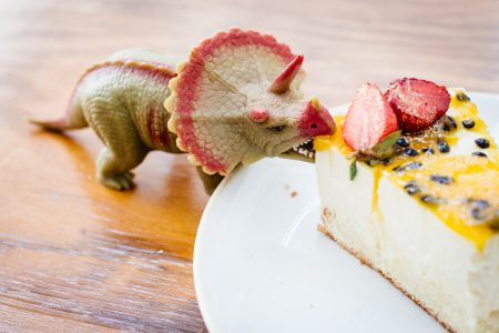 Rubber toy dinosaur about to eat a cake 3 - free stock photo