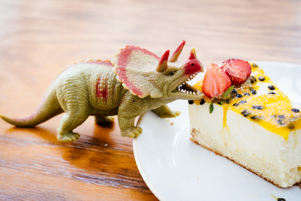 Rubber toy dinosaur about to eat a strawberry on a cake - free stock photo