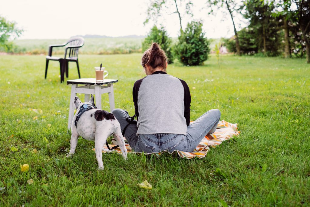 Female having a coffee outdoors with a frenchie - free stock photo