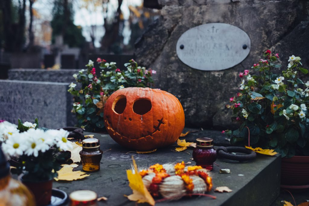 A carved pumpkin on an old grave at the cemetery - free stock photo