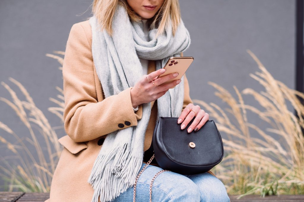 Female holding her phone and purse on an autumn day - free stock photo
