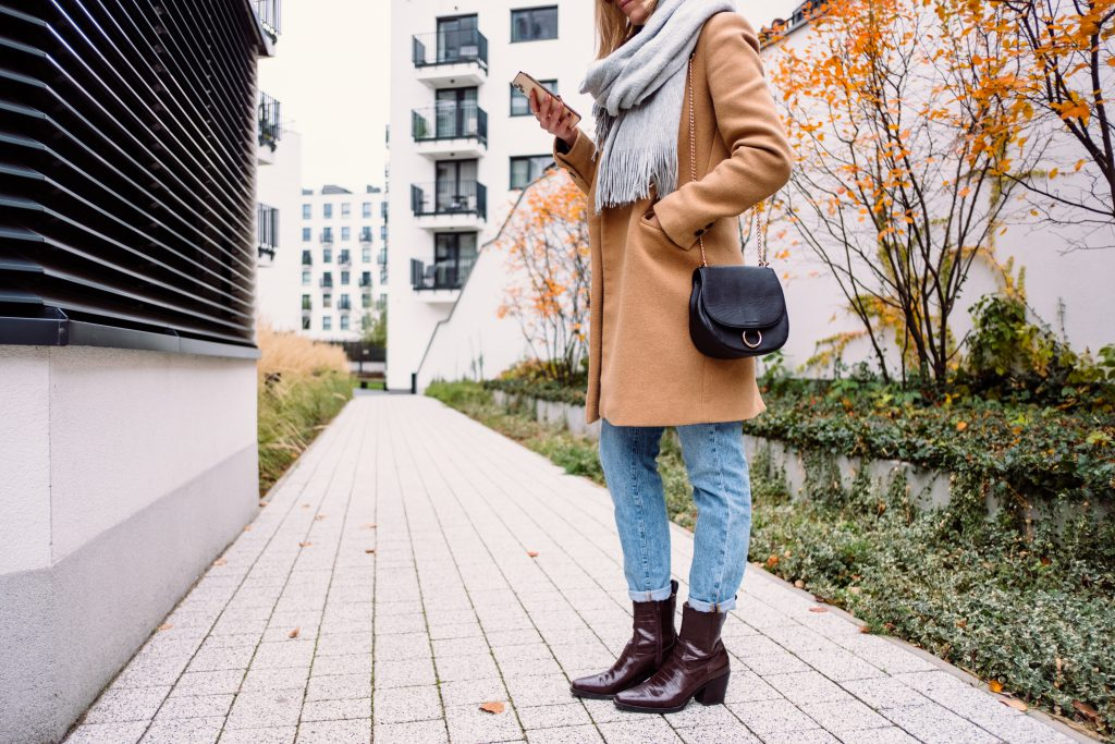 Female holding her phone on an autumn day - free stock photo