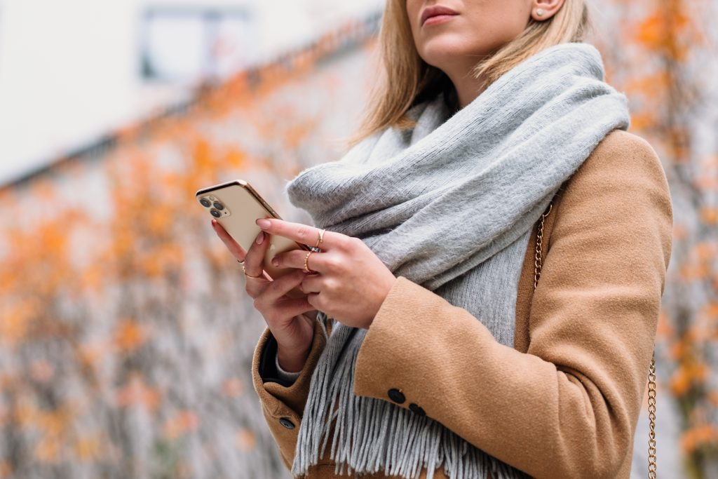 Female holding her phone on an autumn day closeup - free stock photo