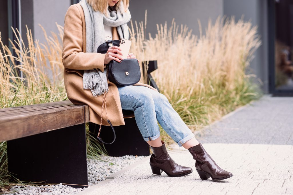 Female looking for something in her purse on an autumn day - free stock photo