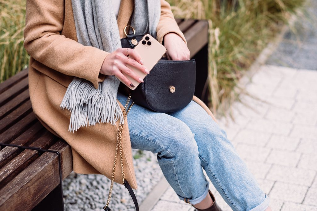 Female looking for something in her purse on an autumn day 2 - free stock photo
