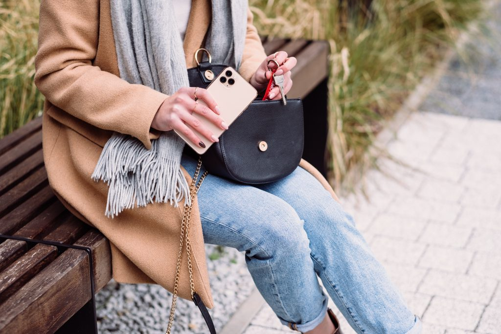 Female taking out the keys from her purse on an autumn day - free stock photo