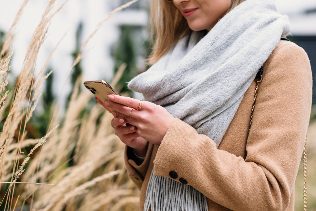 Smiling female holding her phone on an autumn day - free stock photo